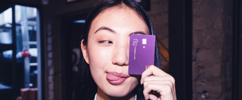 Jovem mostrando a língua com um cartão Nubank no rosto