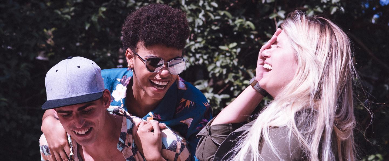 NuConta: Um homem e duas mulheres rindo juntos