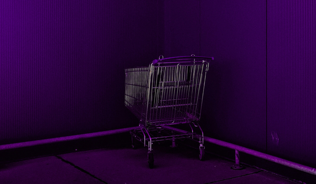 Desafio 52 semanas: um carrinho de supermercado roxo posicionado em um canto formado por duas paredes, ambas roxas.