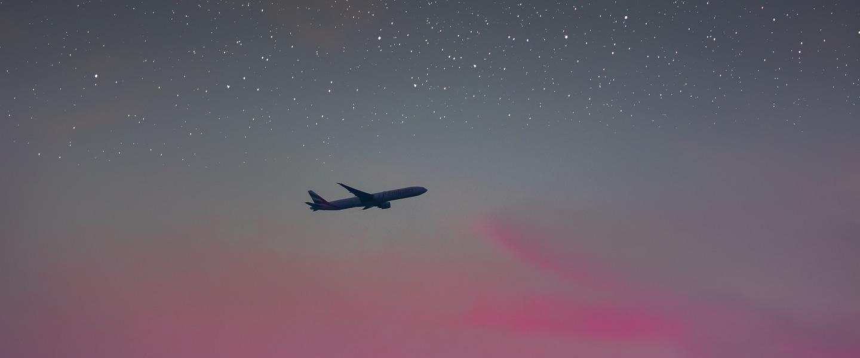 avião sobrevoando um céu de início de noite, com a parte de cima estrelada e a parte de baixo em tons de rosa
