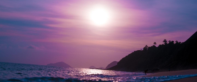 Por do sol em uma praia do nordeste brasileiro com o céu em tons de roxo refletindo no mar