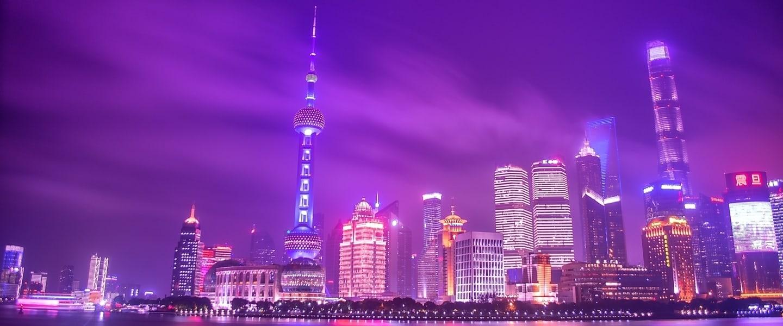 Skyline de Xangai a noite, com o céu roxo e reflexos dos prédios roxos e rosas na água