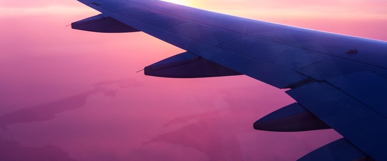 Asa de avião sobrevoando um céu em tons rosados