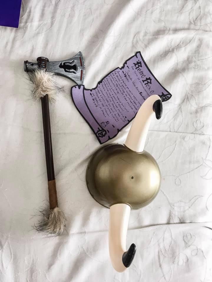 Imagem de um machado e capacete viking de plástico ao lado de uma cartinha roxa escrita à mão.