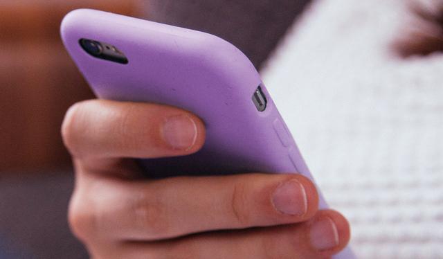 Mão segura celular com capa roxa