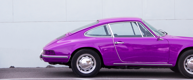 Viagem de carro: um veículo roxo estacionado em frente de uma parede cinza