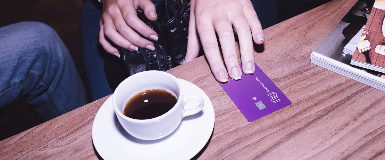 Mesa com uma xícara de café sobre um pires e um cartão de crédito Nubank. Uma mão está segurando o cartão