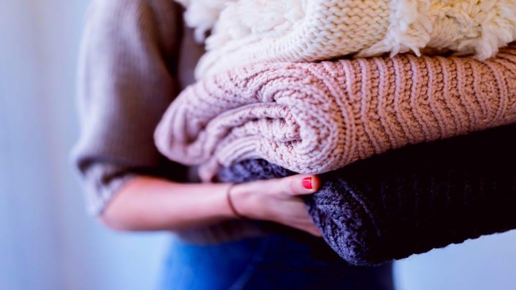 Mulher carregando uma pilha de malhas de tricô