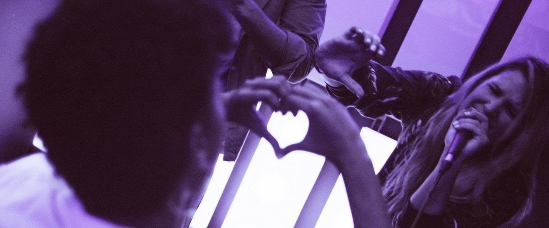 imagem com filtro roxo de um fã fazendo um coração com as mãos para uma cantora no palco