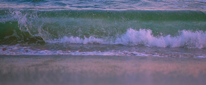 Moeda estrangeira: a imagem, em tons de roxa, azul e roxo, traz uma onda quebrando na beira do mar.