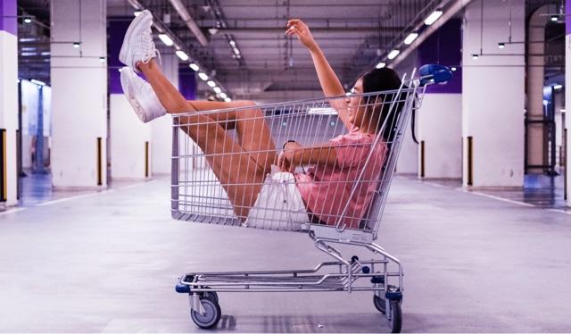 Foto de uma menina dentro de um carrinho de supermercado.