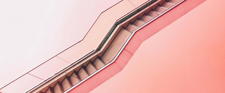 escada rolante na horizontal em frente a um fundo rosa claro