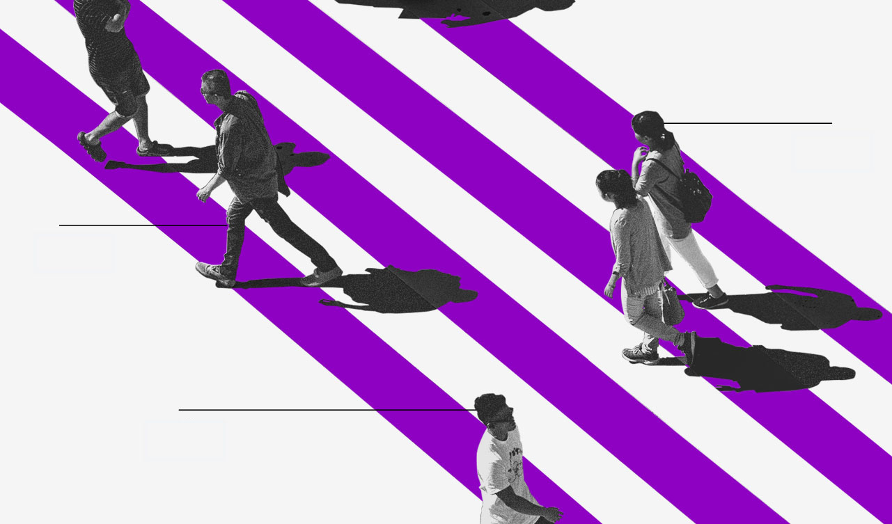 Pessoas em preto e branco caminhando sobre uma faixa de pedestres roxa e branca