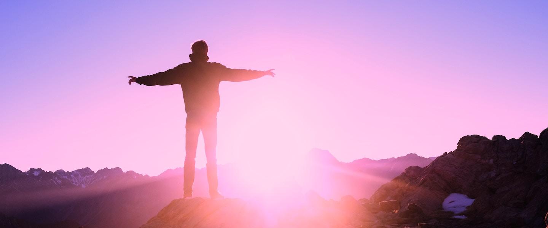 5 tarifas bancárias que você não precisa pagar em uma conta digital: homem de costas com os braços abertos no topo de uma montanha ao pôr do sol.