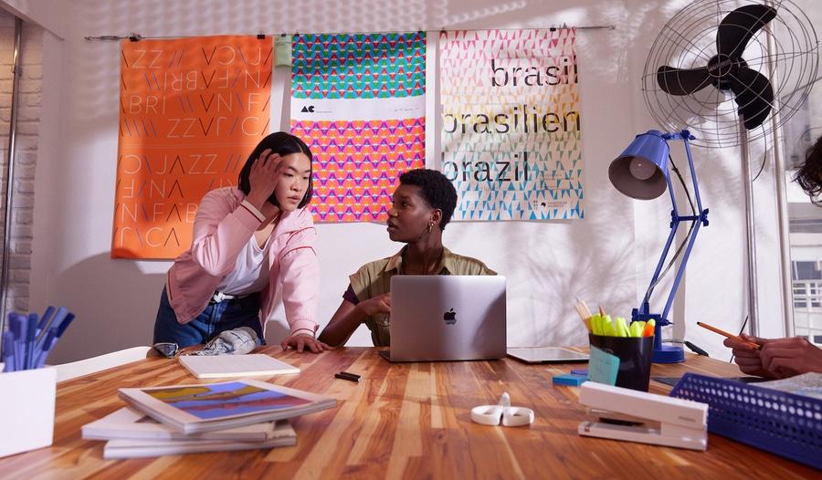 Extrato FGTS: Duas jovens conversando. Uma está sentada em uma mesa, com o computador na frente, e a outra está de pé, olhando para a tela