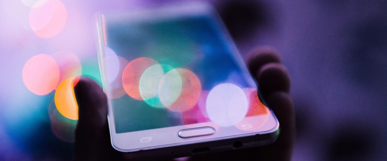 Uma mão segurando um celular com o fundo em tons de roxo.