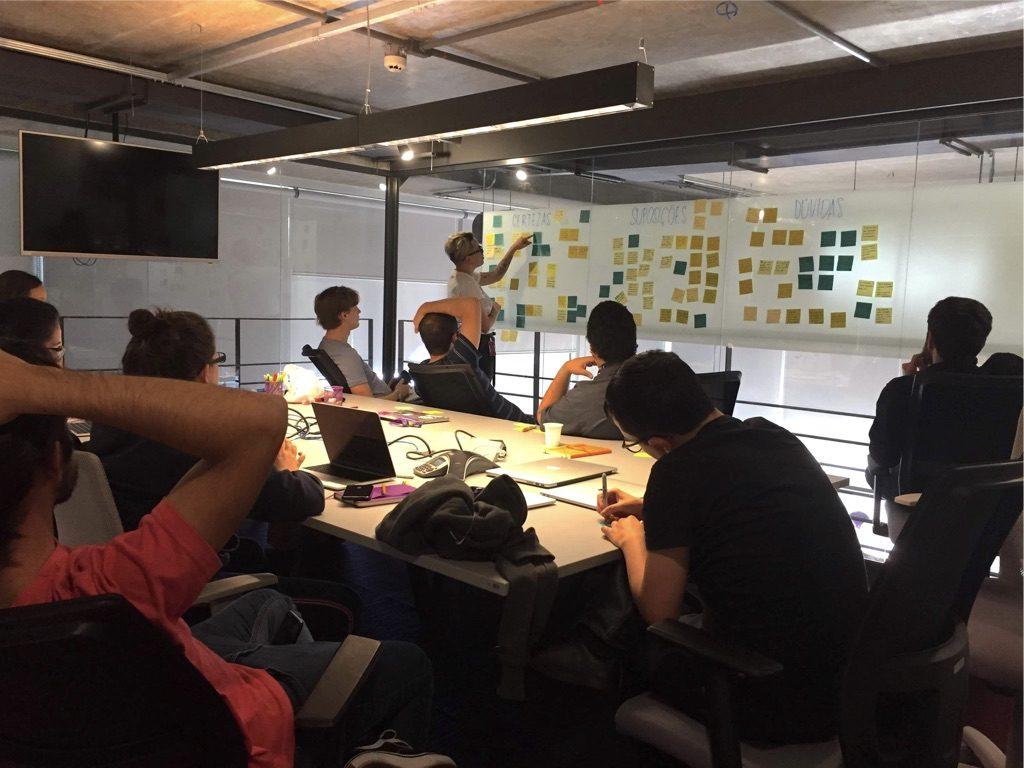 Grupo de pessoas em uma sala, sentadas em uma mesa. Uma delas está de pé colocando post-its na parede