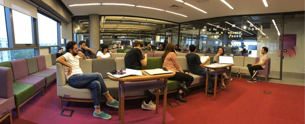 Desenvolvimento de produto no Nubank: time sentado em uma sala de apresentação, em poltronas coloridas