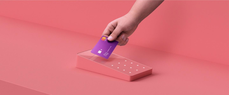 Função Débito Nubank: mão aproxima o cartão roxo do Nubank de uma maquininha rosa. O fundo da foto é todo rosa, da mesma cor da máquina.