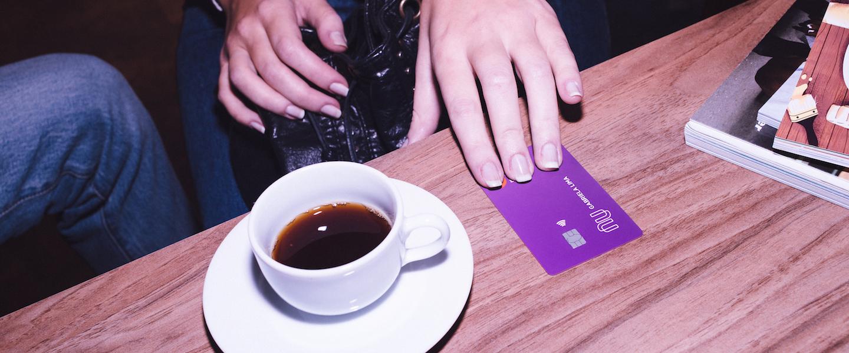 Nubank é confiável: em cima de uma mesa de madeira está uma xícara branca com café, um cartão roxinho do Nubank com uma mão sobre ele e duas revistas.