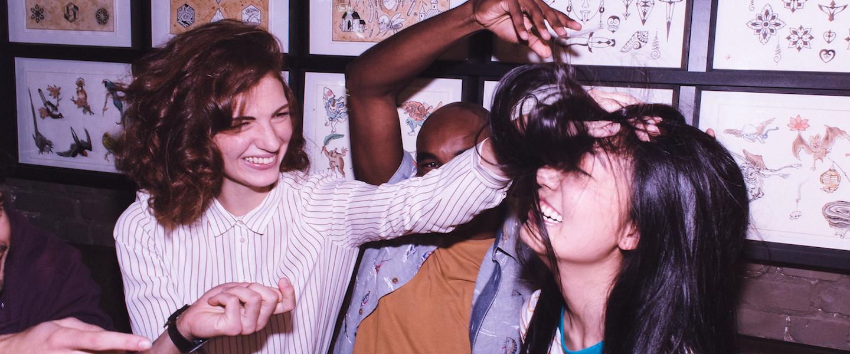 NuCommunity: três pessoas sentadas no banco de um estúdio de tatuagem, sendo que uma mulher está mexendo no cabelo de outras e todos sorriem.