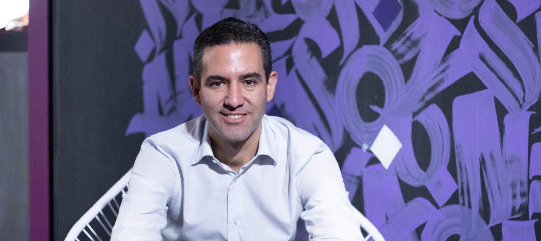 David Vélez Nubank: foto de David Vélez sentado em uma cadeira branca na frente de uma parede grafitada em roxo. David veste uma camisa azul clara, calça jeans escura e um relógio no pulso esquerdo.