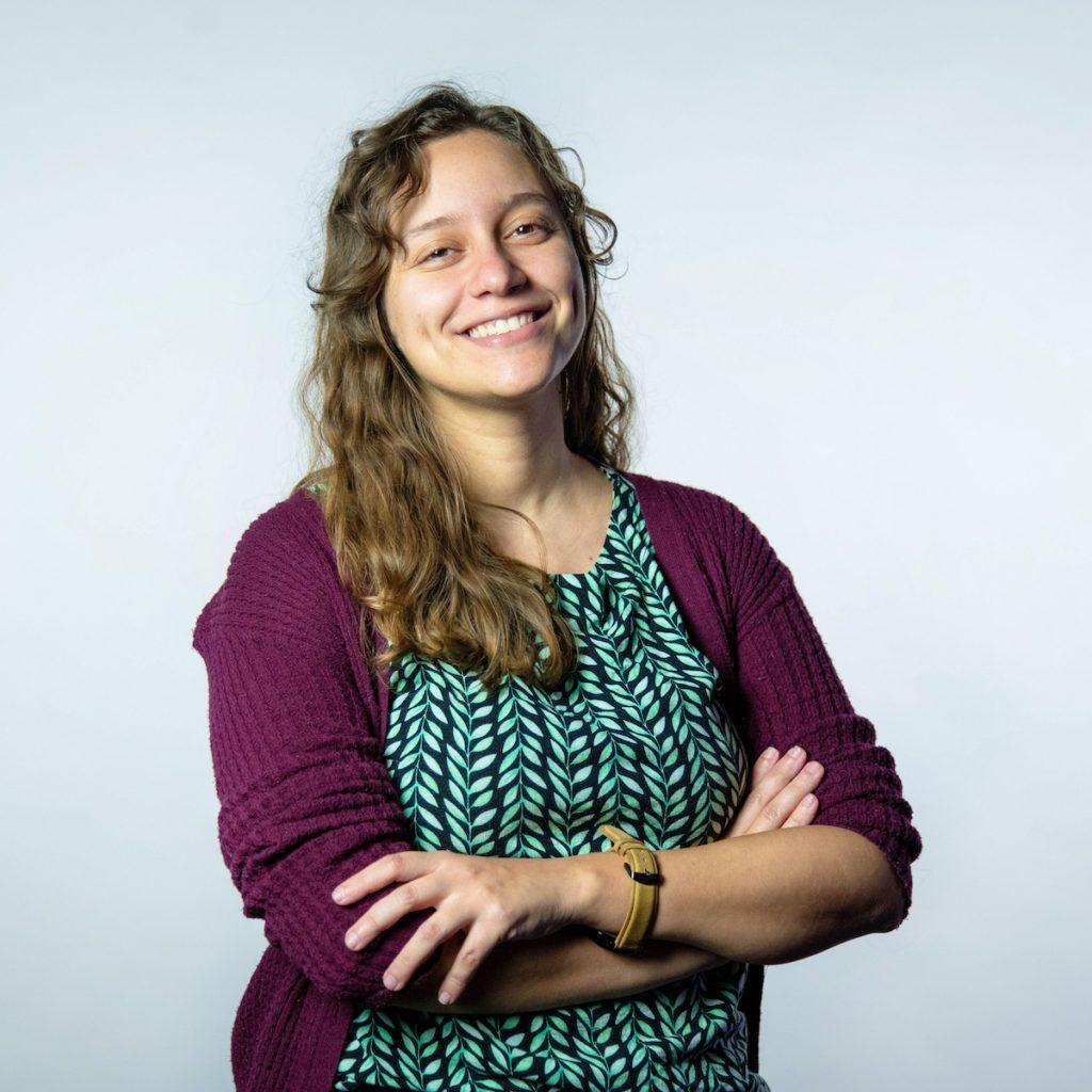 Foto da Jullie Utsch, engenheira de software do Nubank. Ela veste um cardigan vinho, uma blusa verde e está com os braços cruzados. Ela é loira, tem os cabelos ondulados, está sorrindo e tem covinhas na bochecha.