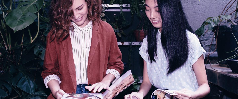 RDB do Nubank: duas moças sentadas lendo revistas, olhando para as páginas e sorrindo