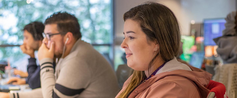 Vagas Nubank: três pessoas trabalhando em seus computadores apoiados na mesa. No primeiro plano está uma mulher loira com um leve sorriso.