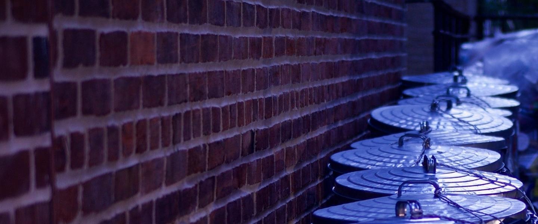 Várias latas de lixo perto de uma parede de tijolinhos