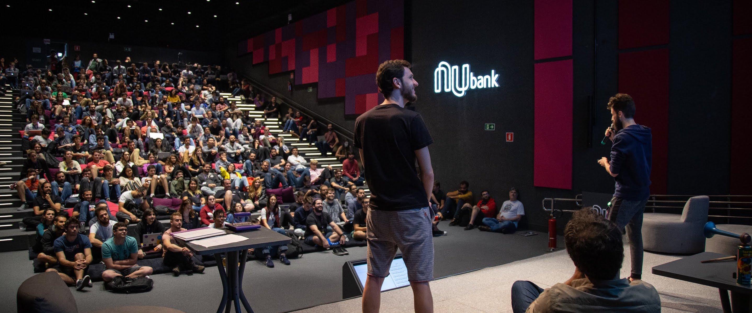 Como são o Coffee Break e a MegaDemo no Nubank: auditório lotado com apresentador na frente