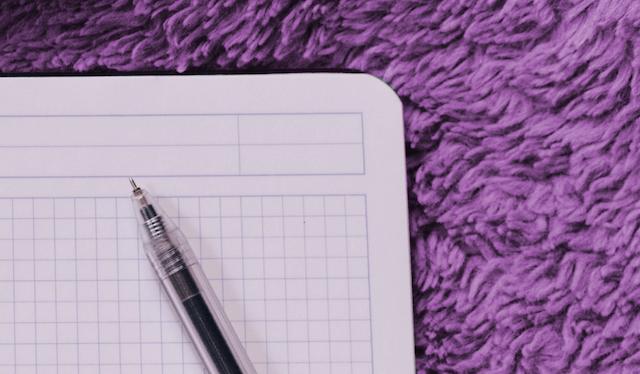 Caderno quadriculado em branco com uma caneta em cima sobre um tapete roxo