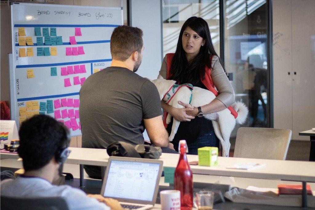 Agile Nubank: foto mostra duas pessoas conversando em pé - um rapaz, de costas, e uma mulher de frente para ele segurando um cachorro branco