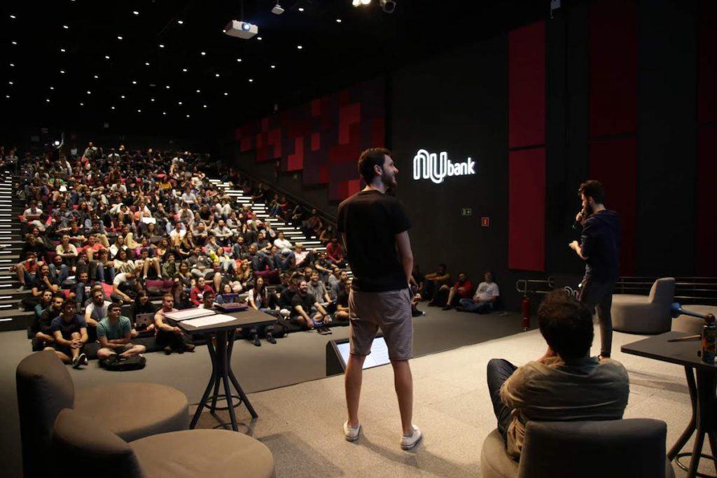 Dois homens em um palco apresentando para uma plateia no auditório do Nubank