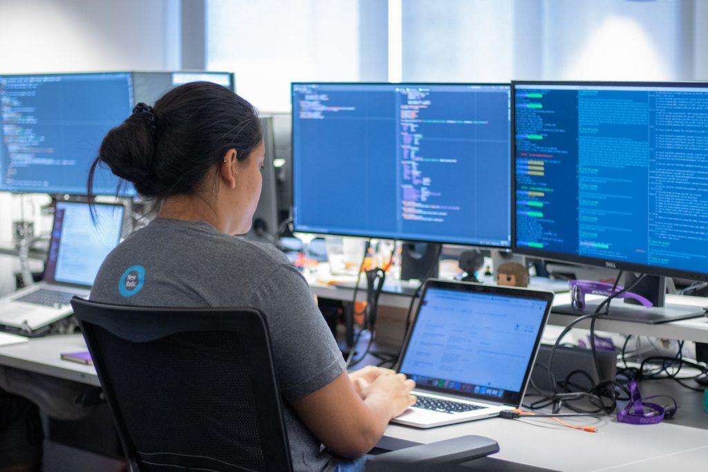 Uma mulher trabalha com código de programação em três telas de computador.