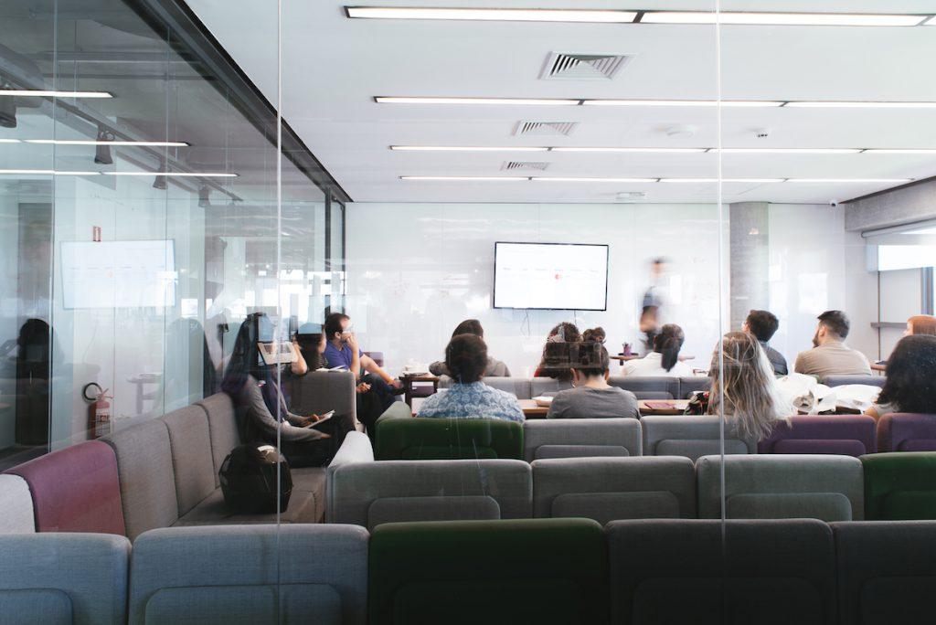 Sala de reunião com diversas pessoas sentadas nos sofás enquanto outra apresenta.