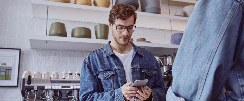 Conta PJ Nubank: imagem mostra jovem de óculos e jaqueta jeans, atrás de um balcão de café, olhando para o telefone