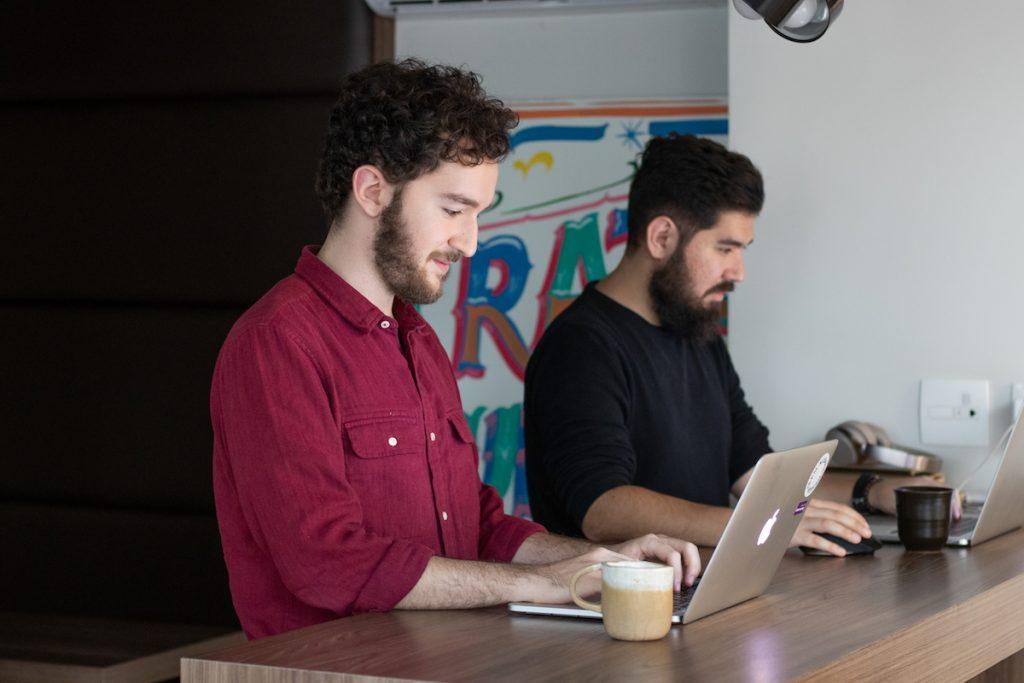 Dois homens trabalhando em seus computadores de mão numa bancada de madeira.