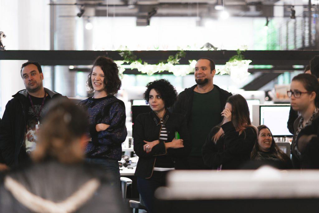 Um grupo de pessoas em pé no escritório sorrindo e olhando para o lado