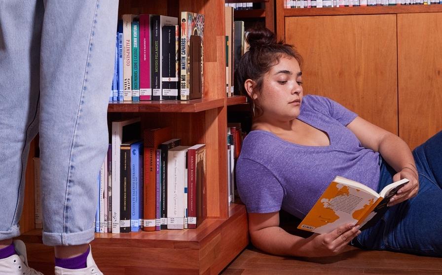 Negociar dividas: mulher deitada no chão encostada em uma prateleira lendo um livro