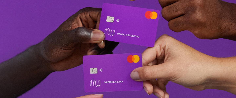 Mãos segurando cartões Nubank em um fundo roxo