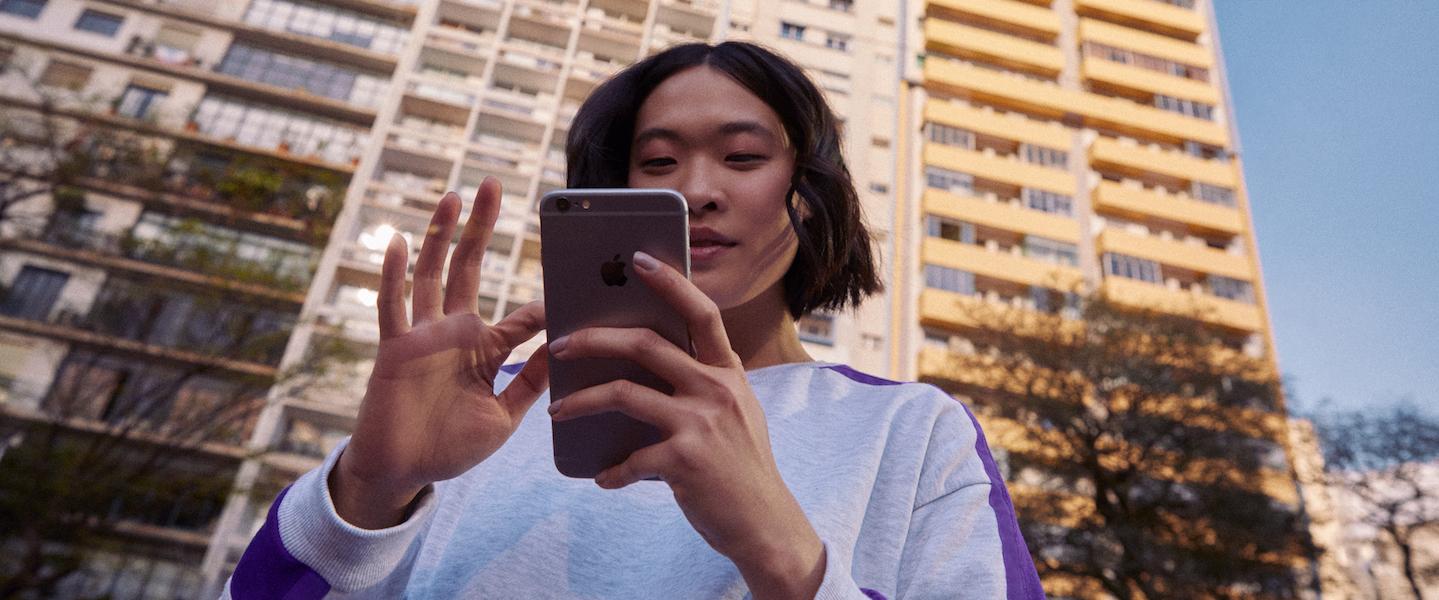Nubank fora do ar: jovem de cabelos curtos e blusa branca usa seu telefone