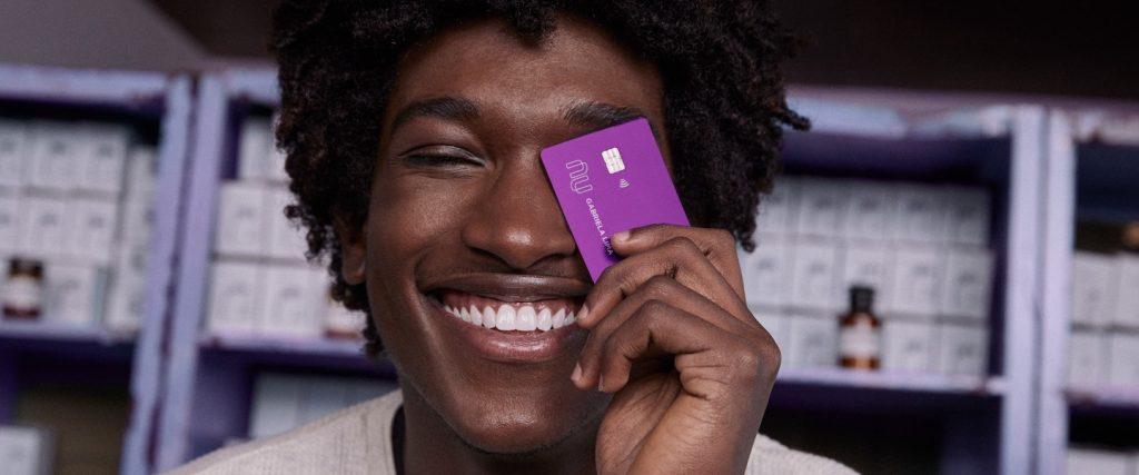 Nubank milhas Smiles: homem sorrindo segurando um cartão de crédito Nubank na frente do rosto