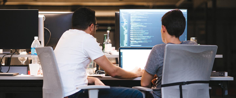 Engenharia de software Nubank: dois homens sentados olhando para um computador. Na segunda tela, um programa de código de programação.