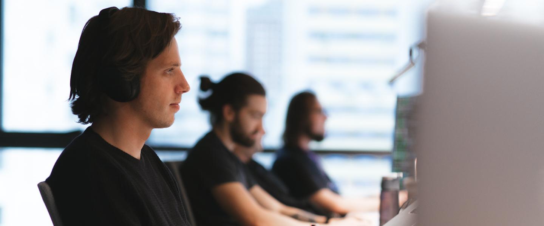Machine learning: foto de um homem trabalhando. Ele veste preto, usa fones de ouvido e está digitando no teclado. Mais ao fundo, outros dois homens também estão trabalhando em seus computadores.