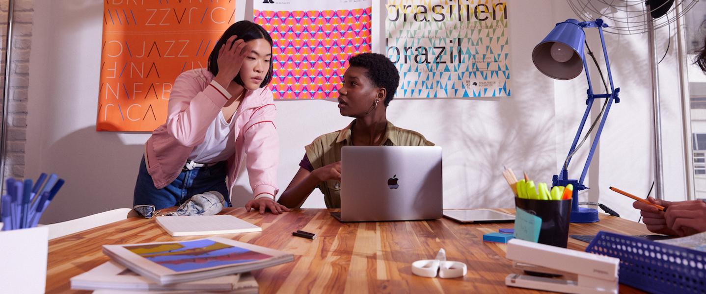 Simulador NuConta: foto mostra duas jovens conversando em frente a uma parede de post its. Uma delas está sentada em uma mesa, com um computador aberto