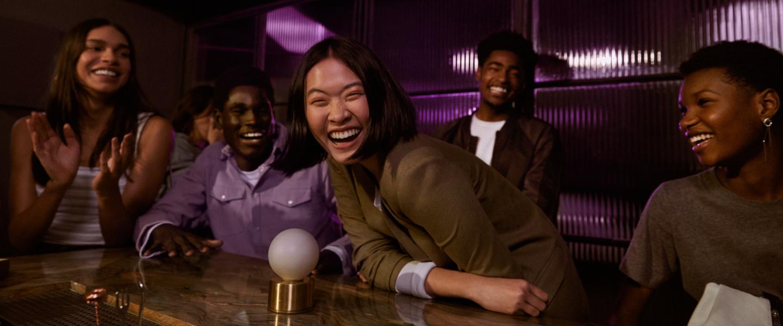 NuConta: amigos reunidos em uma mesa de restaurante, todos vestindo roxo, dão risada