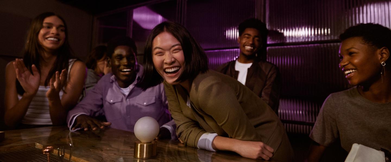 amigos reunidos em uma mesa de restaurante, todos vestindo roxo, dão risada