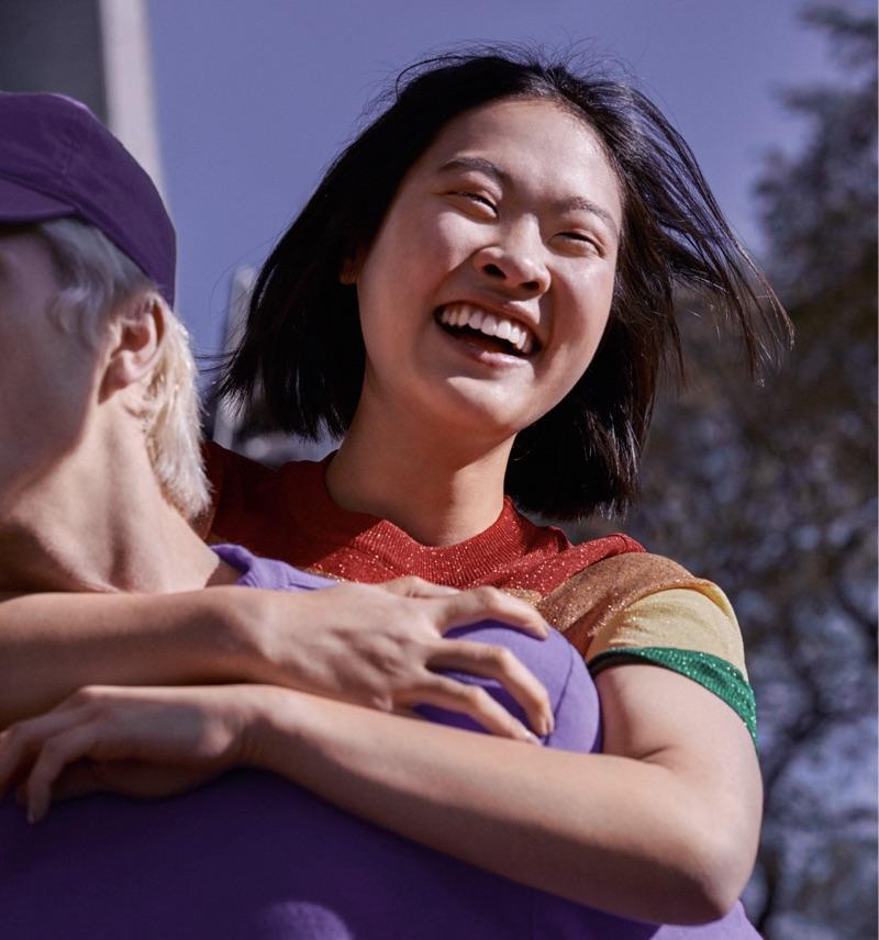 Conta conjunta: jovem com blusa colorida está sorrindo, abraçada nas costas de um rapaz de camiseta roxa