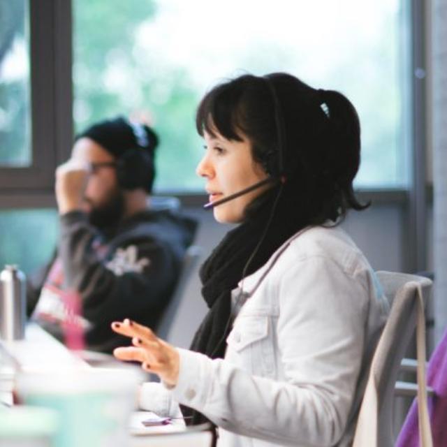 Atendimento Nubank: Três pessoas trabalhando no escritório do Nubank. O foco da foto está em uma mulher, jovem, atendendo clientes com um headphone
